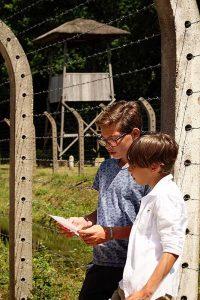 Kinderen lezen de namen en leeftijden voor van de afgevoerde kinderen tijdens het kindertransport